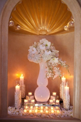Wedding reception wall niche with vase and white flowers and votive candles