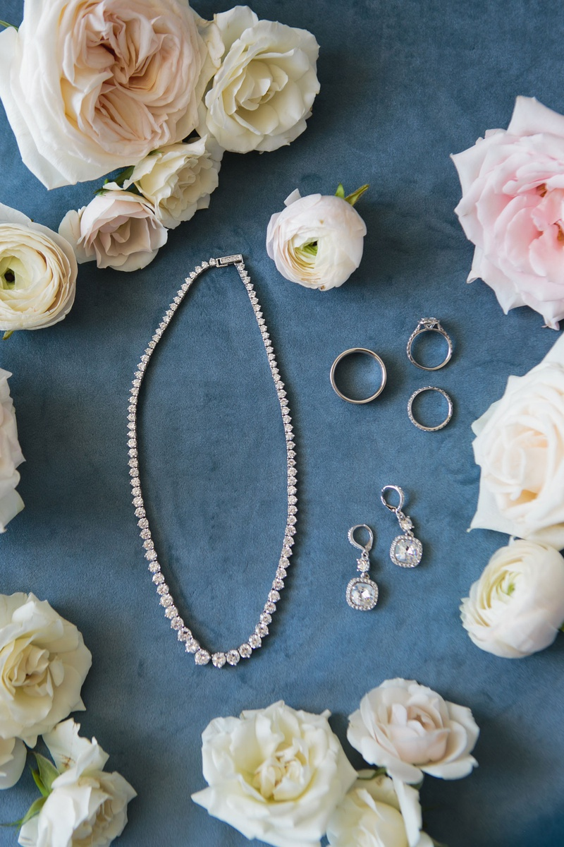 bride jewelry and accessories wedding rings, necklace, and earrings surrounded by garden rose flower