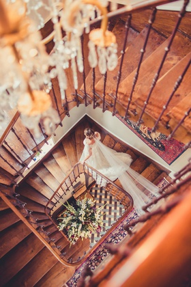 bride in wedding dress and long homemade handmade veil walking down wood staircase at french venue