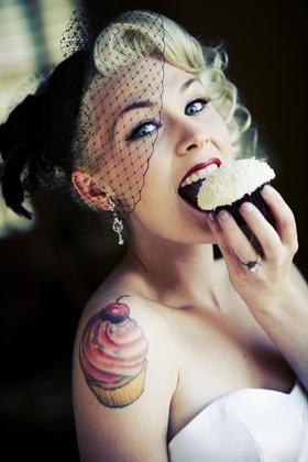Bride in a black wedge veil eats a Sprinkles cupcake