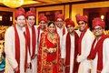Indian bride in a red lehenga and veil with gold and red embroidery with groomsmen in sherwanis