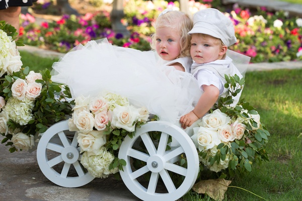 Blonde flower girl and ring bearer in white wagon with rose decorations