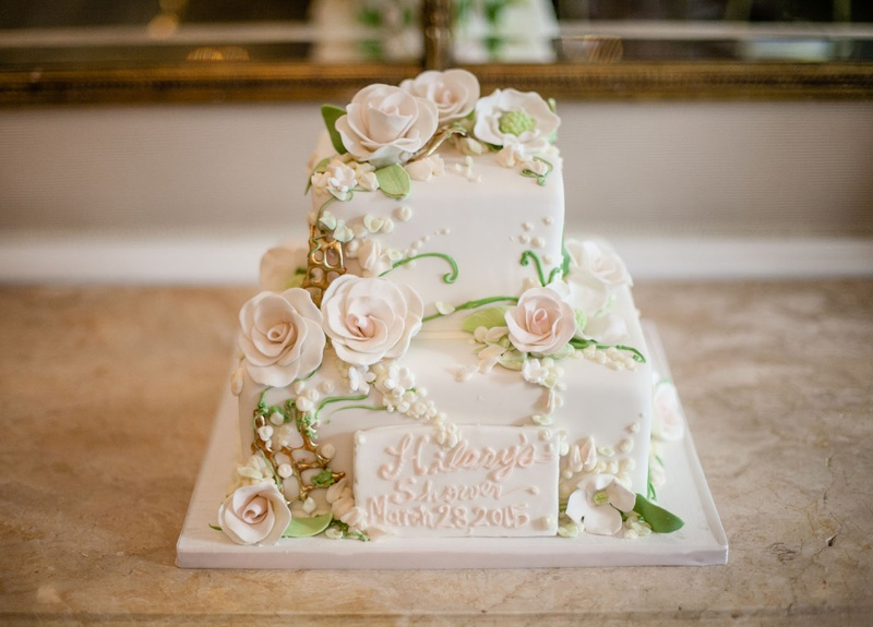 two layer white cake with sugar roses and gold details for bridal shower