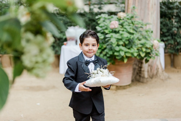 Ring bearer in tuxedo carrying pillow with flowers on top