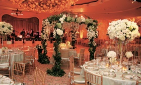 Wedding sweetheart table is placed under a canopy of greenery, green, and white flowers.