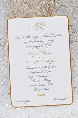 Script calligraphy font with monogram on black tie wedding invitation on top of wedding dress