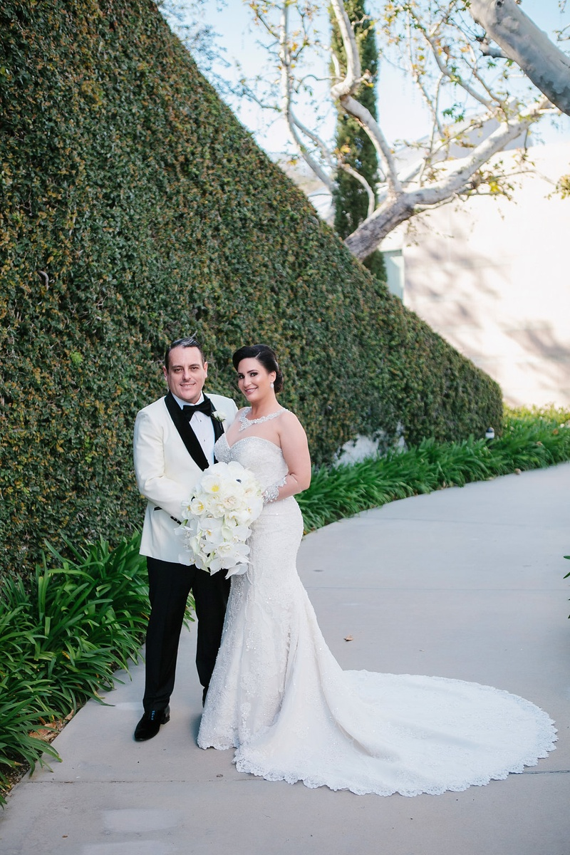 bride in martina liana trumpet gown with illusion neckline and sleeves, groom in white tuxedo jacket
