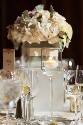Wedding reception table with white flowers and a floating candle in a glass candle holder