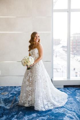 bride with hair worn down long strapless wedding dress flower applique sheer details white bouquet