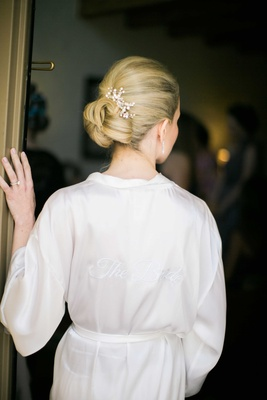 bride shows off her bun hairstyle and hairpiece with crystals in bridal robe getting ready