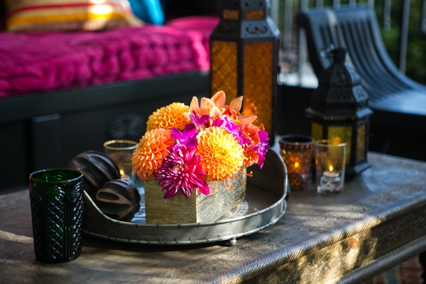 Orange chrysanthemums, hot pink orchids in gold rectangular vase at engagement party