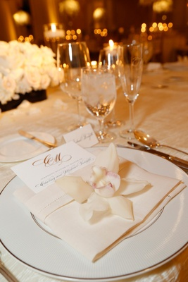 Wedding reception place setting with white china charger, linen napkin, white orchid, menu