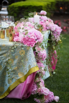 Pink flowers and vines cascade from table