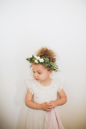 adorable flower girl in frilly dress with flower crown with lots of greenery
