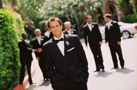 Groom in a black tuxedo with a matching bow tie and a white boutonniere and pocket square
