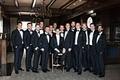 groom in white tie and tuxedo, groomsmen in black ties and tuxedos, large group of groomsmen