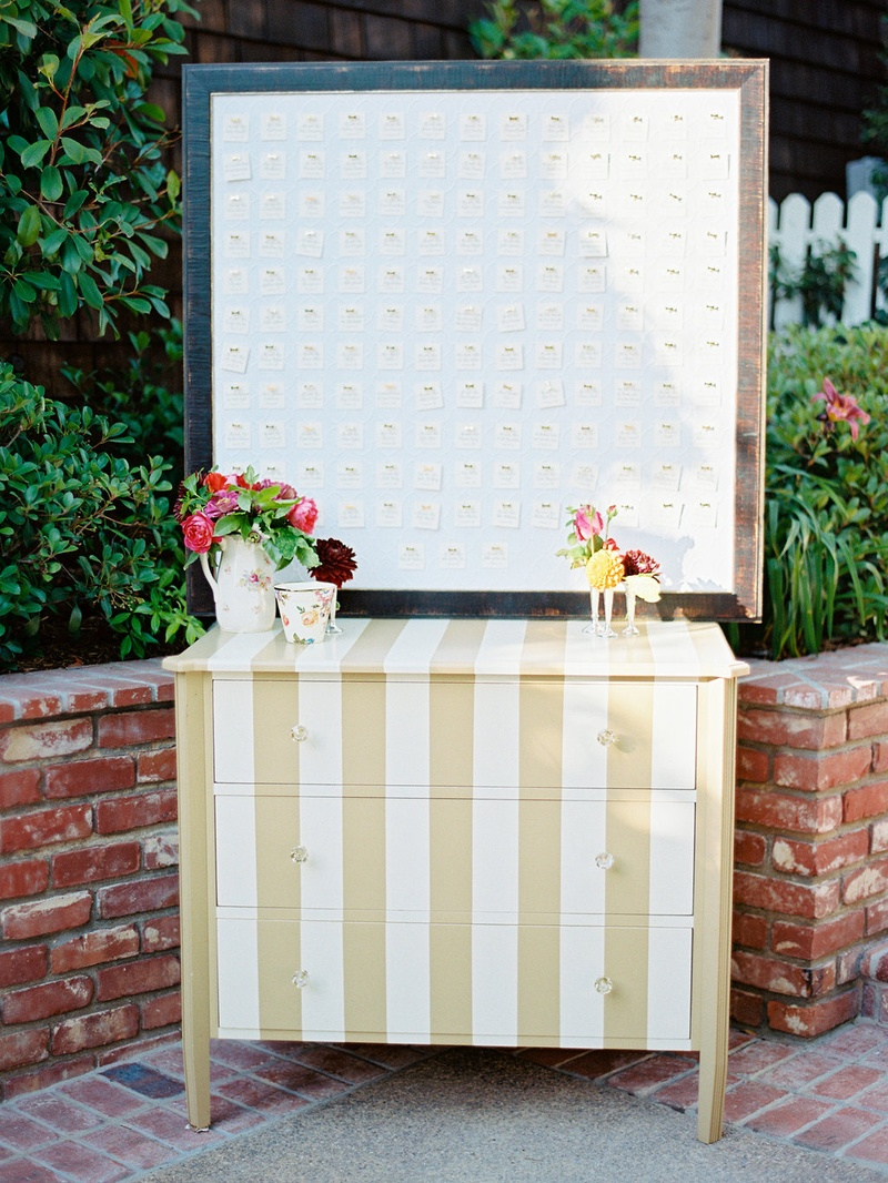 Gold and white stripe dresser with frame of escort cards pinned to board with gold bow pins