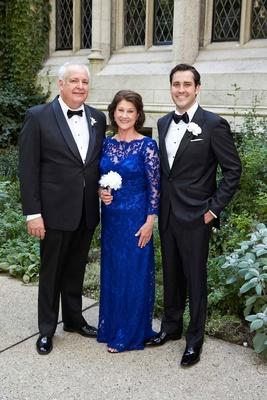 Groom in tuxedo with mother of bride in floor length cobalt blue mother of bride dress lace sheer