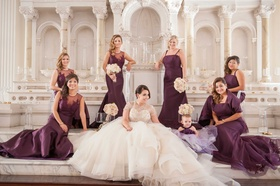 Bride in white and gold ball gown with six bridesmaids in long purple bridesmaid dresses