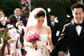 groom and bride carrying pink bouquet walk up the aisle