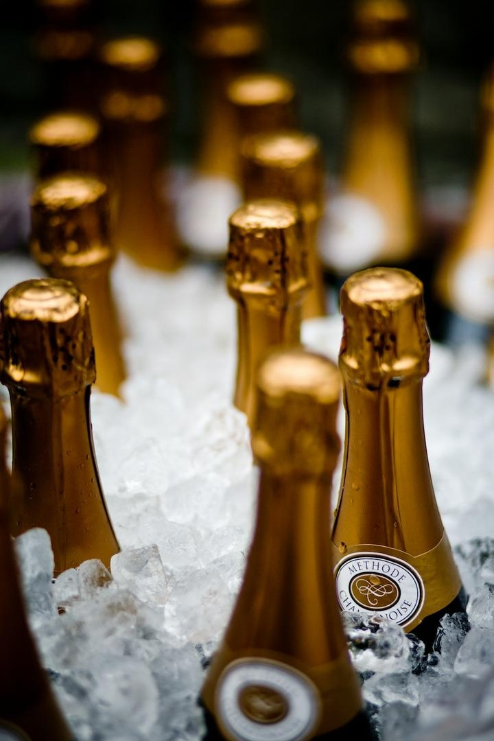 Gold champagne bottles in bucket of ice at wedding reception