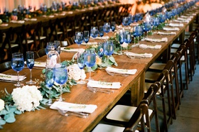 Wedding reception long farm tables wood with wood chairs garland down center greenery blue glasses