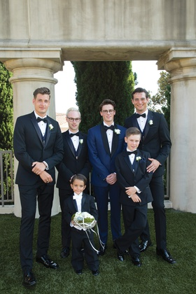 groom in navy tuxedo, groomsmen in black tuxedo, junior groomsman, ring bearer with white tie