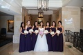 Bride wearing ball gown with bridesmaids in eggplant dresses