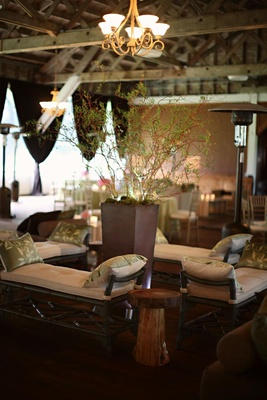 wooden benches topped with green pillows surrounding tall centerpiece of branches