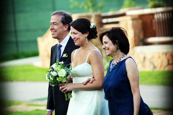 Bride walks down aisle with mother and father