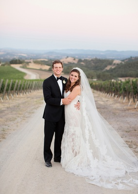 Man in tuxedo and woman in wedding dress at winery