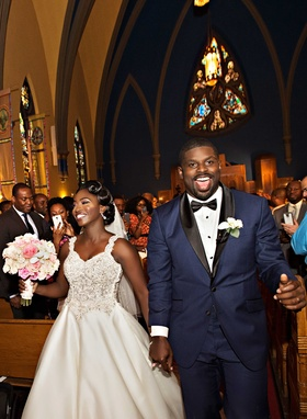 Bride and groom in navy tuxedo during recessional at Chicago church wedding ceremony