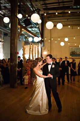 Bride in a strapless Monique Lhuillier gown dances with groom in a tuxedo