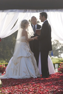 Bride and groom stand on red flower petals at altar with officiant