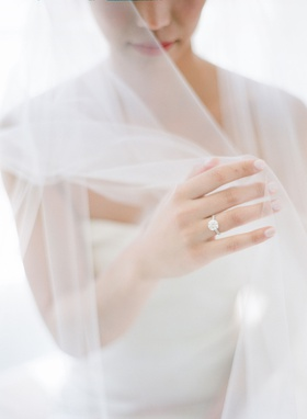 bride with romantic veil over face with arms underneath strapless gown round diamond engagement ring