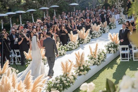 outdoor wedding ceremony white aisle runner pampas grass white flowers bride processional father