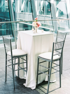 high silver gray chairs white table linen small candles blush ivory flowers urban background
