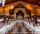 Wedding ceremony lined with candles in hurricanes with rose petals at the base