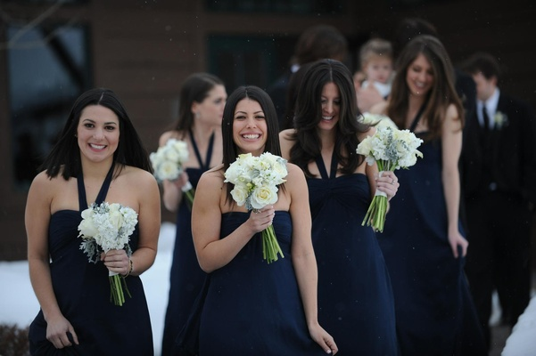 Winter wedding bridesmaids in snow with white bouquets