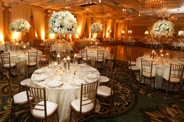 Wedding reception with draping, warm lighting, centerpieces of white hydrangeas, roses, orchids