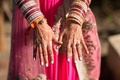 Henna designs on Indian bride's hands with bangles