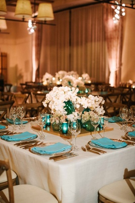 Blue napkin on gold rim charger plate wood tray in center with white flowers turquoise candleholders