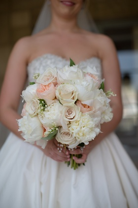 Bride's bouquet of white and peach peonies, white roses and pale pink roses