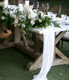 wooden head table with soft fabric runner and garland of greenery and flowers, pillar candles