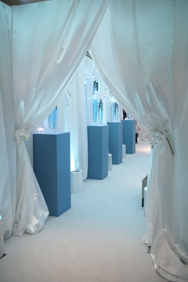 white curtains leading to blue and white reception