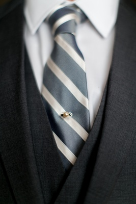Groom's grey suit, grey and white striped tie, with pearl and dark gemstone pin