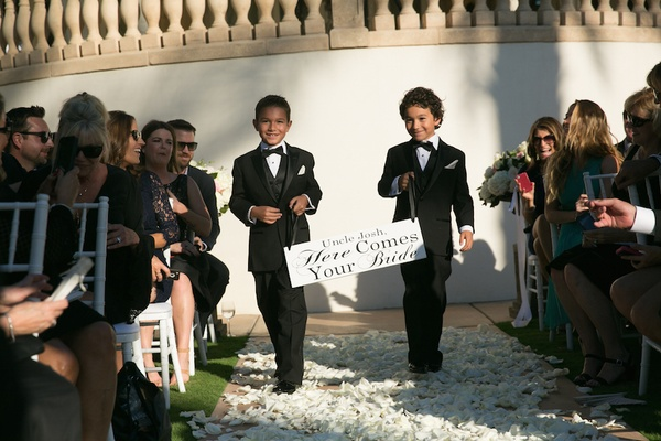Young boys in tuxedos walking down the aisle with poster