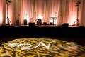 Wedding reception with a gold damask and monogram projection on the dance floor