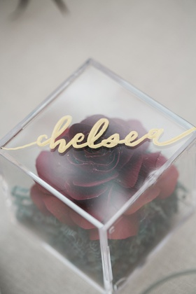 place card and bridal shower favor with paper rose inside of acrylic box with gold calligraphy