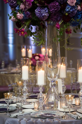 hurricane candles on elaborate stands surround floral centerpiece of roses and hydrangeas